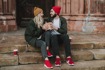 Full length portrait of excited happy girl accepting beautiful gift box from her boyfriend. They looking at each other and smiling while sitting on steps with cups of coffee