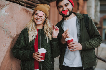 Waist up portrait of charming girl in hat covering eye with pink paper heart while her boyfriend hiding lips behind red paper heart. They looking at camera and smiling