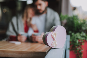Close up of pink heart-shaped gift box with bow waiting for lady at outdoor cafe