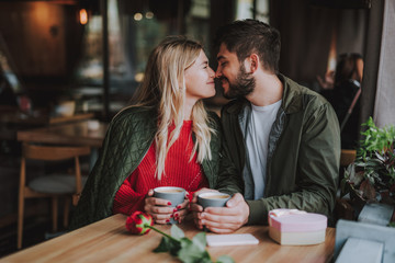 Romantic date. Charming girl and her boyfriend sitting at the table and holding cups of coffee