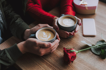 Close up of male and female hands holding cups of hot drink with foam. They sitting at the wooden table with red rose, cellphone and gift box