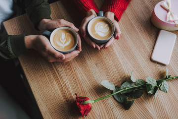 Top view close up picture of male and female hands holding cups of hot drink with foam. They sitting at the table with cellphone, red rose and gift box