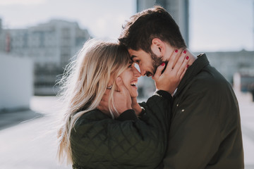 Beautiful young couple feeling happy while touching foreheads