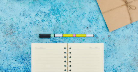 concept of recording your daily affairs on your desktop. Notepad on a blue abstract background. Copy space layout. place for text. view from above.