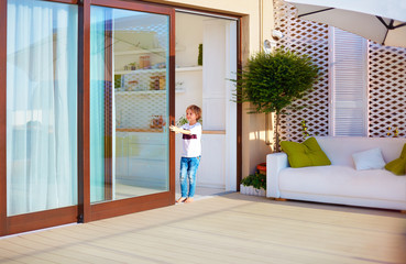 happy young boy, kid opening the sliding door on rooftop patio area at home