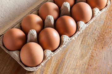 Brown chicken eggs in carton on wooden table.