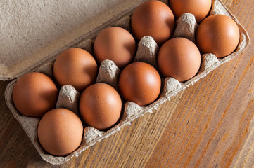 Ten brown chicken eggs lay in a carton on a wooden table. View from above.