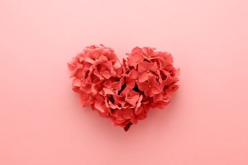 Valentine's Day card. Living Coral color of the Year 2019. Heart shape made of flowers abstract background. Love concept.