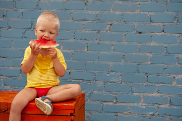 Funny village children eat watermelon sitting on old chest in courtyard of village house. Boys brothers are happy together. School holidays in village. Parents take care of kids. Eco-friendly products
