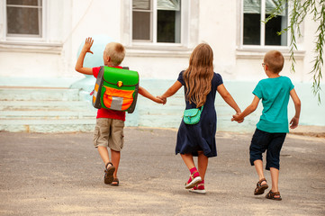 Children return to school. beginning of new school year after summer holidays. Boys and girl with school bags play among flowers near school building. Education for kindergarten and preschool children