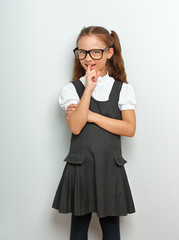 Thinking smiling pupil girl in fashion eyeglasses gnawing the finger and have an idea in school uniform on blue background