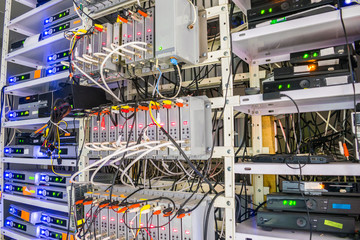 Racks with telecommunication equipment is in the server room of the data center. Many coaxial wires are connected to the switching modulators of the television station.