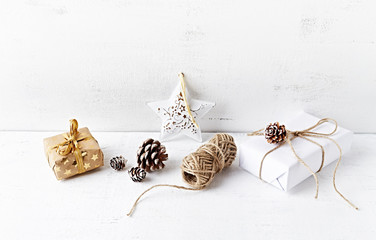Christmas presents, decorations, cones and a twine on white painted wooden background. Copy space. Symbolic image