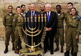 Israeli PM Netanyahu and American Ambassador Friedman pose for a photo together with Israeli soldiers as they take part in a candle lightning ceremony on the Jewish holiday of Hanukkah at the Western Wall in Jerusalem's Old City