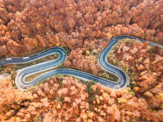 Winding road from high mountain pass, in autumn season. Aerial view by drone. Romania