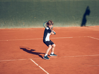 Boy playing tennis on hard court