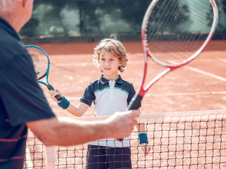 Old man and boy with tennis rackets near net on hard court