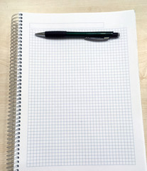 Top view of open spiral blank notebook with pencil on white desk background