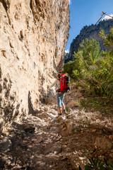 Traveler climbs along narrow mountain gorge