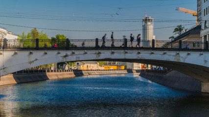 people crossing the city's canal at the hump-backed bridge