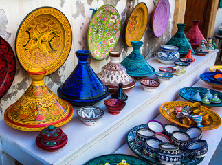 Moroccan pots for the traditional delicious dishes Tajine and Couscous with  colorful decorative ornamental painting on a market in the Medina of Essaouira in Morocco, Africa