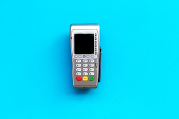 Payment terminal, compact POS terminal on blue background top view copy space