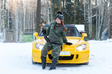Beautiful young woman with pretty red braids posing with paintball marker near sport car