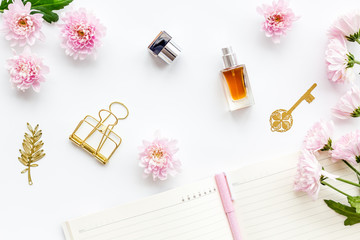 Perfume on feminine desk. Women's accessories. Perfume near notebook for dairy, vintage key among flowers on white background top view