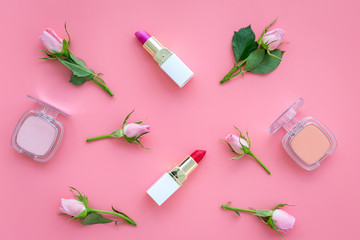 Rose tone cosmetics. Lipstick, bulk, eyeshadow among rose flowers on pink background top view