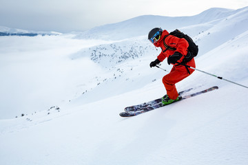 Fototapete - A boy is skiing fast down the hill