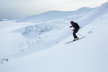 Fototapete - A girl is skiing fast down the hill in Carpathian mountains.