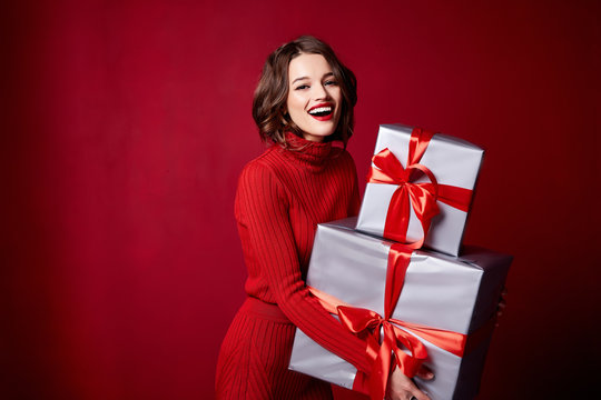 Beautiful young sexy woman thin slim body evening makeup fashionable stylish dress clothing collection, brunette, gifts boxes red silk bows holiday party birthday New Year Christmas Valentine's Day.