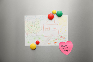 Kid's drawing and magnets on refrigerator door