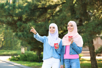Muslim women with cups of coffee walking in park
