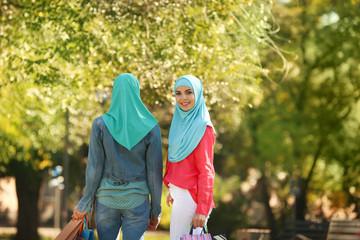 Muslim women walking in park on sunny day