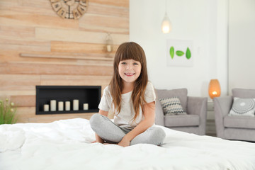 Cute little girl sitting on bed at home