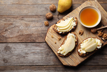 Toasted bread with tasty cream cheese and pear on wooden table, flat lay. Space for text