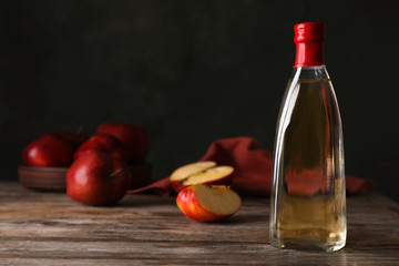 Composition with bottle of apple vinegar on table. Space for text