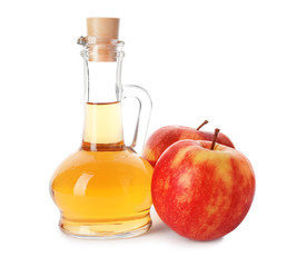 Glass jug of vinegar and fresh apples on white background