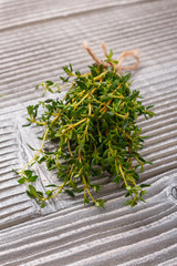 essential oil of thyme on a gray wooden rustic background
