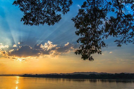river sunset / landscape of beautiful sunset on river colorful blue sky with tree branch foreground - sunset on mekong river asia