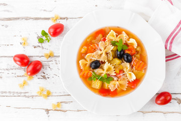 Minestrone, vegetarian soup with pasta and vegetables on white wooden rustic background. Traditional italian food. Top view