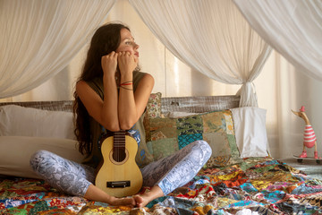 Girl with a guitar on a canopy bed, house, hotel, boho style