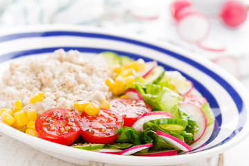 Oatmeal porridge with vegetable salad of fresh tomatoes, corn, cucumber and lettuce. Light, healthy and tasty dietary breakfast. Top view