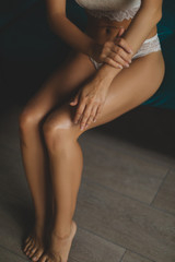 Young woman smearing cream on her leg. Epilation concept. Woman in white lingerie. Erotic