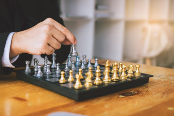 Businessman thinking about strategy concept and hand moving the king in a chess game for win.