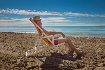 Man in hat relaxing on beach, looking at sea