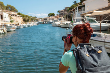 Young woman taking pictures of smal yacht port