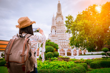 Asian woman tourists are taking photos of the Wat Arun temple on vacation Bangkok Thailand.
