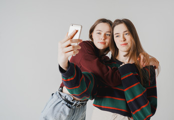 Two sisters twins beautiful girls in casual doing selfie on smar